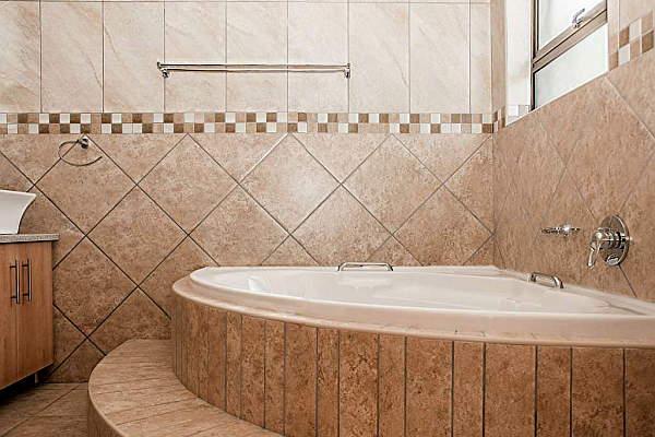 Bathrroom with a corner bathtub.
